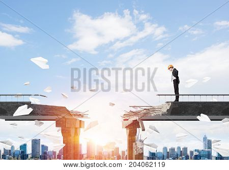 Young engineer in suit and helmet looking down while standing among flying paper planes on broken bridge with cityscape and sunlight on background. 3D rendering.