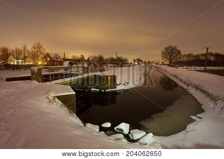 Night shot of a little river in a cold winter night with fresh snow.