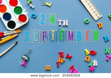 September 24th. Day 24 of month, Back to school concept. Calendar on teacher or student workplace background with school supplies on blue table. Autumn time.