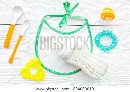 Mother care breast milk in bottle and infant formula powdered healthy food with bib for baby feeding on white wooden table background top view