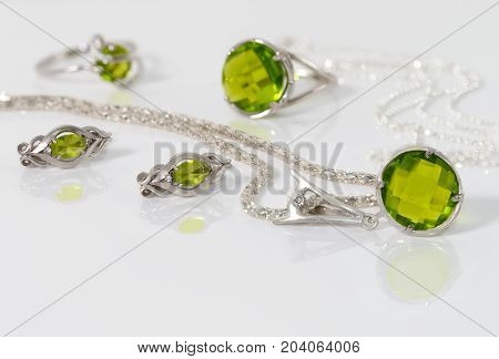 Close-up beauty silver pendant earrings with peridot on background chain and rings on white acrylic desk.