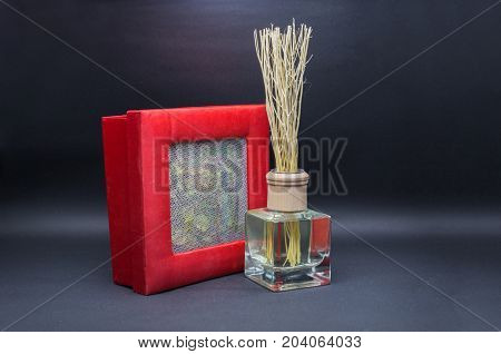 Aroma Oil And Dry Tea Leaf In Net And Inside Paper And Silk Red Box