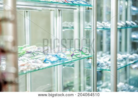 Various Of Eye Glasses On The Shelf In The Optic Shop. Selective Focus. Space For Text