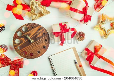 Top view Christmas holidays composition with gifts in craft paper with red satin ribbon, decor, watch and notebook on the white wooden background with copy space for your text. Selective focus