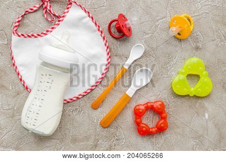 preparation of mixture baby feeding with infant formula powdered milk on gray stone background top view