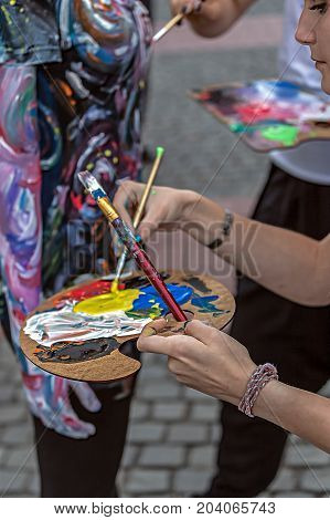 TIMISOARA ROMANIA - SEPTEMBER 8 2017: Girls make body painting of a woman. 3D art symbolizing on live at the street inside the CheckART Carnival organized by the City Hall Timisoara. Liberty Square