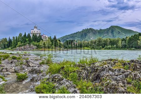Picturesque summer landscape of rocky island on the mountain river Katun (Altai Republic Russia) and part of hotel building