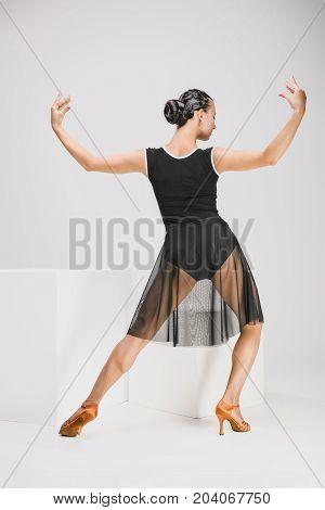 pretty woman in black and transparent dress in studio, nice dancer dancing backwards