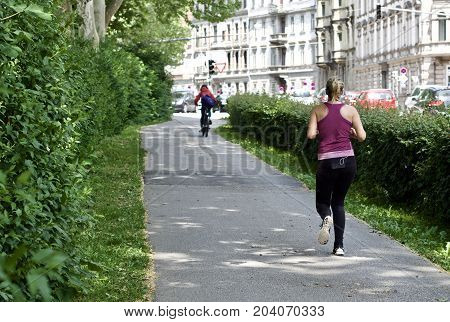 young woman is running near the park