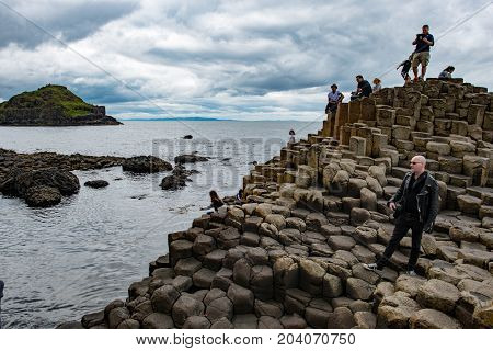 COUNTY ANTRIM, NORTHERN IRELAND - AUGUST 27, 2017: View of Group of tourists exploring the Giant's Causeway