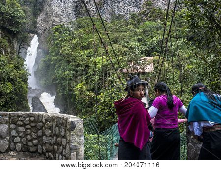 Banos de Agua Santa Cascades route Ecuador - May 1 2012: Indigenous women walk across the bridge under Devil's Cauldron waterfall (spanish: Pailon del Diablo) - Mountain river and fall in the Andes