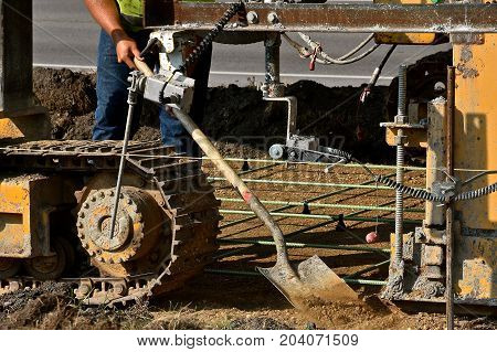 Man shoveling  sand as a cement laying machine spreads concrete on a new sidewalk.