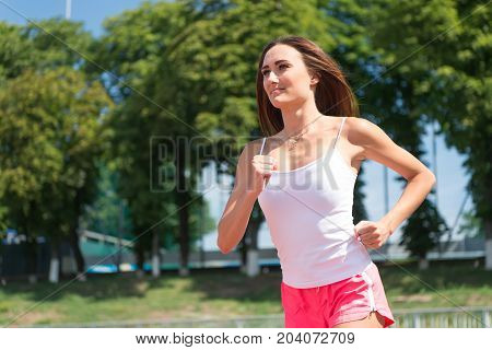 Runner on competition and future success. Girl sunny outdoor on blue sky. Woman running on arena track. Sport and healthy fitness. Coach or trainer at workout.