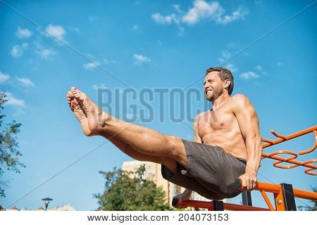 Sportsman exercising on parallel bars outdoors on blue sky. Man training abs by raising legs. Athlete with bared muscular torso six pack biceps triceps. Fitness and sport. Healthy lifestyle concept