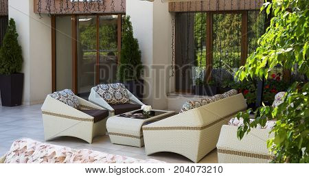 Set of luxury wicker furniture on summer garden terrace outdoor, free space. Table and chairs in empty cafe. Wicker furniture rattan chairs and sofa on terrace