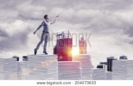 Man in casual wear keeping hand with book up while standing on pile of documents with cityscape and sunlight on background. Mixed media.