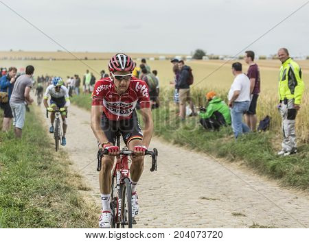 QuievyFrance - July 07 2015: Environmental portrait of the Belgian cyclist Tim Wellens of Lotto-Soudal Team inside the peloton riding on a cobblestoned road during the stage 4 of Le Tour de France 2015 in Quievy France on 07 July2015.