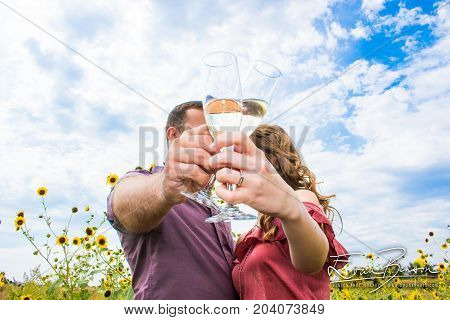 Happy Couple Engagement Photo Just Engaged Toasting With Champagne With Blue Sky and Wild Flowers in the Country Just Married