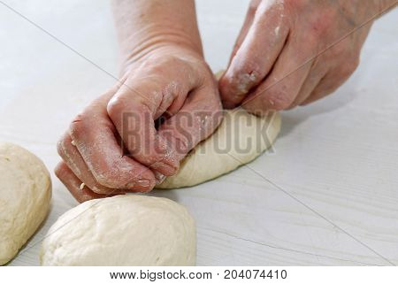 Woman unrolls dough on a table, woman knead the dough