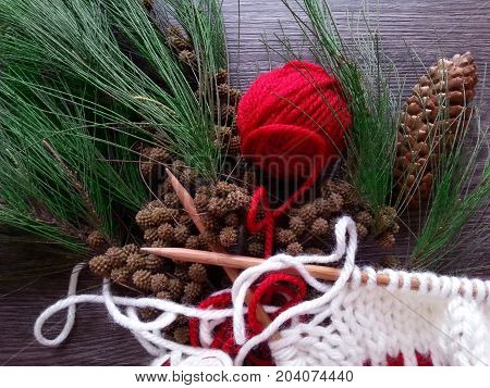 Red yarn ball, white knitted garment, pinecone and Christmas tree branches on dark wood background