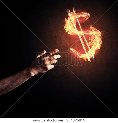 Close of man hands pointing at fire glowing dollar sign