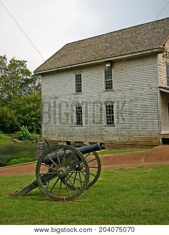 a civil war cannon in front of an old gristmill