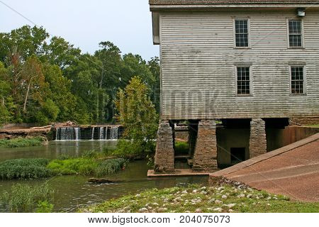 water flows over a low dam next to a gristmill