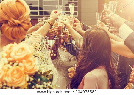Wedding Guests Clinking Champagne Glasses With The Newlyweds In The Background. Vintage Tone