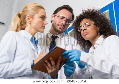 Group Of Scientific Workers Taking Notes Making Research In Laboratory, Mix Race Team Of Scientists Writing Results Of Experiment Or Diagnosis In Tablet In Lab