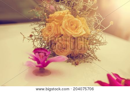 Close-up Of Wedding Bouquet Made Of Yellow Roses On White Limousine Hood. Vintage Tone