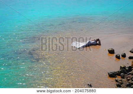 bride or woman in wedding white dress laying on beach in sea or ocean water as mermaid beauty and fashion