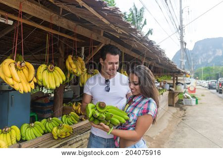 Couple Buying Bananas On Street Traditional Market, Young Man And Woman Travelers Choosing Fresh Fruits