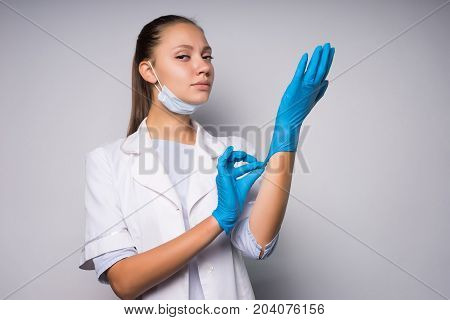 Young female student doctor intern dressing gloves,ready for surgery
