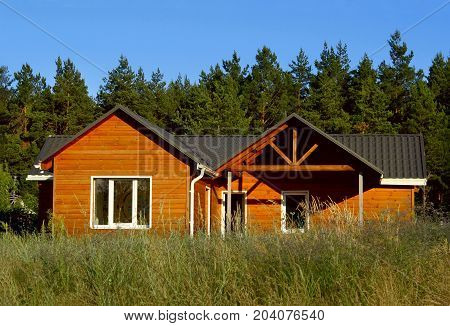 Wooden house in countryside. Ecological Small wooden house. Wooden house with meadow in front of it. Beautiful modern wooden house. Front elevation. Front view.