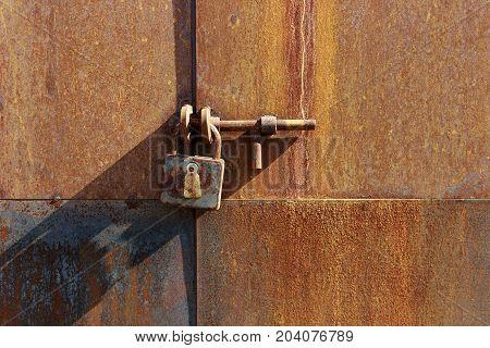 old, rusty lock on an old, rusty door