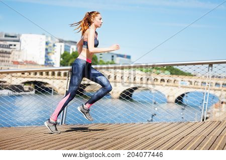 Side view portrait of sporty young woman running across the city streets