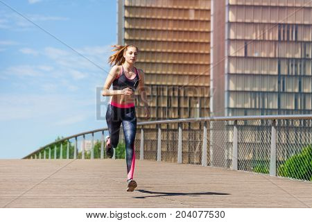 Portrait of sporty young woman running and sprinting outside at racetrack