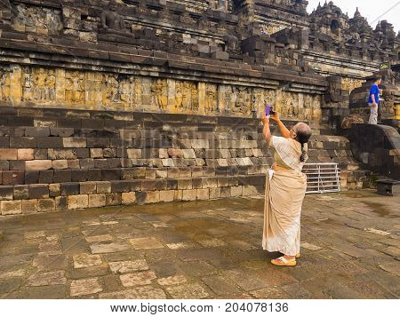 JOGJA, INDONESIA - AUGUST 12, 2O17: Unidentified woman taking pictures of a wall with Bas relief, Borobudur Temple, Location in Central Java, Indonesia.