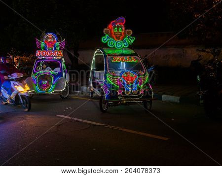 JOGJA, INDONESIA - AUGUST 12, 2O17: A traditional pedicap transport parket at outdoor with colorful and bright lights at night at jogja Yogyakarta Indonesia.