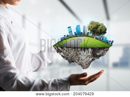 Side view of business woman in shirt keeping green island with road and city in her hands with office view on background. Mixed media.