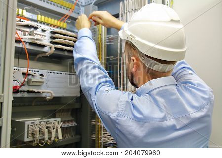 Electrician engineer at work inspecting cabling connection in industrial automation control fuseboard