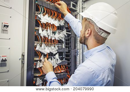 Service engineer in data center. Engineer in white helmet performs connection of optical fiber patch cord in data center. Adjustment of telecommunication systems.