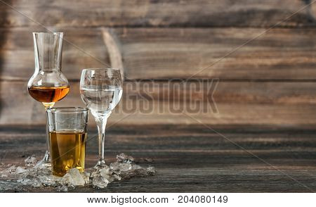 Alcoholic drinks with ice on wooden background. Aperitif whisky liquor vodka