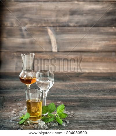 Alcoholic drinks with ice and mint leaves on wooden background. Aperitif whiskey liquor vodka