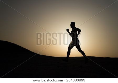 silhouette of running man on sunset fiery sky background in mountain sport and recreation future and success people and nature speed and healthy lifestyle