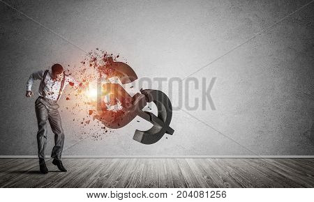 Young furious businessman in empty room crashing with fist stone dollar symbol