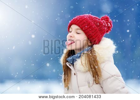 Adorable Little Girl Catching Snowflakes With Her Tongue In Beautiful Winter Park. Cute Child Playin