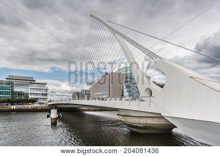 Dublin Ireland - August 7 2017: Closeup of modern Samuel Beckett suspension bridge over Liffey River under heavy cloudscape. Modern office buildings in background.