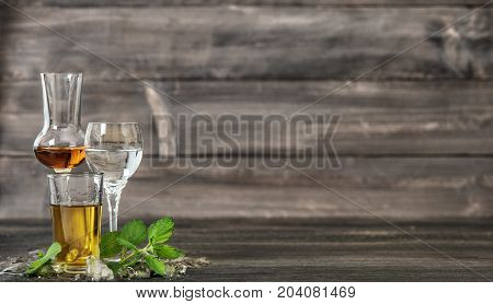 Alcoholic Drinks with ice and mint leaves on wooden background. Aperitif whiskey gin rum vodka. Food beverages