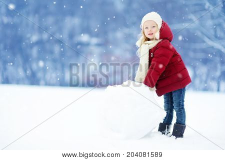 Adorable Little Girl Building A Snowman In Beautiful Winter Park. Cute Child Playing In A Snow.